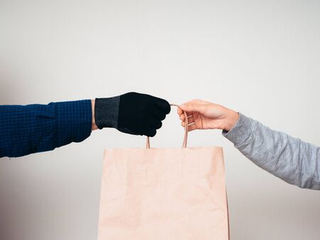 Two hands with a paper bag on a white background. Delivery concept for the COVID-19 pandemic.