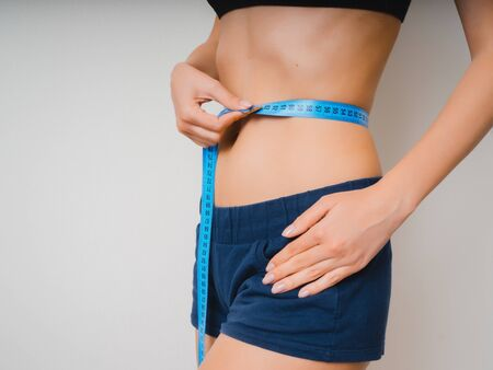 The body of a slender girl in blue shorts on a white background. The concept of weight loss. Stockfoto
