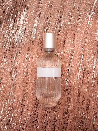 A bottle of perfume lying on a shiny golden fabric. Mock up. Banque d'images