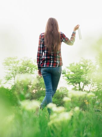 Happy young girl takes off a medical mask and breathes fresh air in nature. Rejoices over the end of the coronavirus pandemic and isolation. Back view.