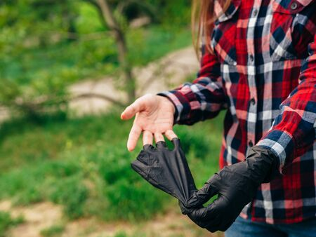 A young girl in a red checkered shirt takes off black latex black gloves on a background of green trees. End covid-2019.