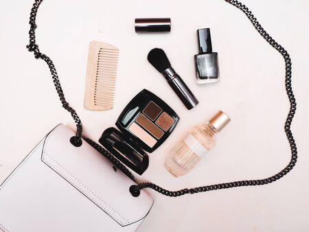 White women's handbag with a set of cosmetics from eyeshadows, brushes, nail polish, perfume and a wooden comb on a white textured background. Flat lay. Banque d'images