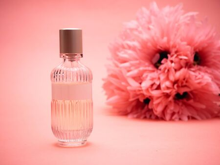 Bottle with perfume on a pink background with flowers.
