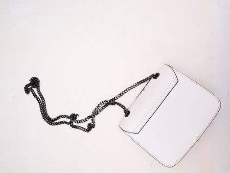 White bag with a black chain on a white textured background. Copyspace. Banque d'images