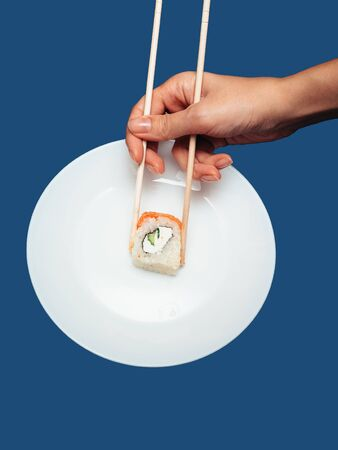 Female hand takes chopsticks sushi rolls with a white round plate on a blue background.