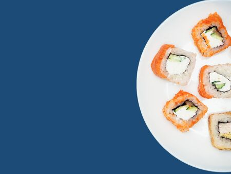 Sushi rolls on a round white plate on a blue background. Copyspace. Banque d'images