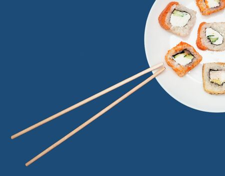 Sushi rolls on a round white plate with chopsticks on a blue background. Copyspace.