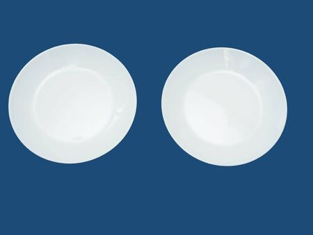 Two round white plates on a blue background.