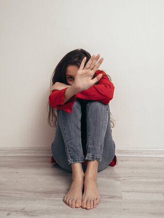A girl in a red shirt and jeans sits sad against the wall. Domestic violence. She raised her hand asking for a stop. Banque d'images