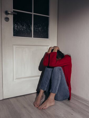 A young girl in a red shirt and jeans sits sad in the corner of the room. Domestic violence. Banque d'images