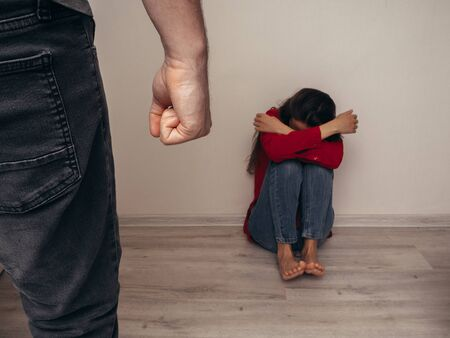 Male fist on the background of a frightened girl in a red shirt and jeans. Domestic violence. Banque d'images