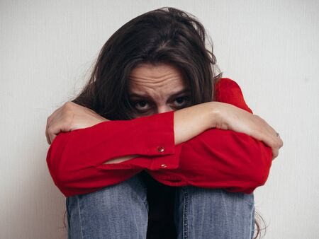 A girl in a red shirt and jeans sits sad against the wall. Domestic violence. Banque d'images