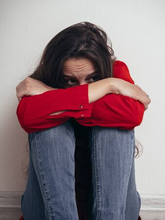 A girl in a red shirt and jeans sits sad against the wall. Domestic violence.
