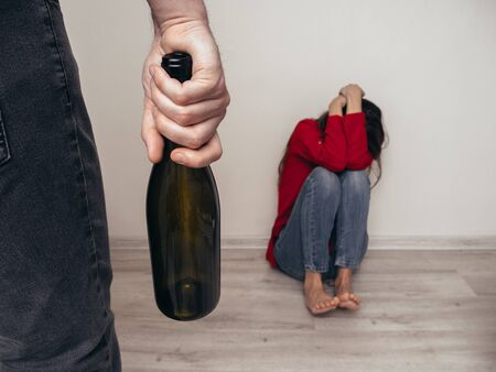 Male hand with a bottle of alcohol on the background of a frightened girl in a red shirt and jeans. Domestic violence. Alcoholism. Banque d'images