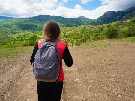 A young girl in a red tank top with a gray backpack in the mountains with green trees and clouds.