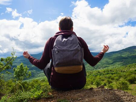 A young guy in a red hoodie and gray backpack travels in the mountains among green trees and clouds. Meditating.