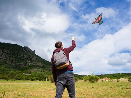 A young guy is playing with a colorful kite on a background of mountains with clouds.