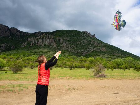 A young girl in a red tank top plays with a multi-colored kite on a background of mountains and clouds.