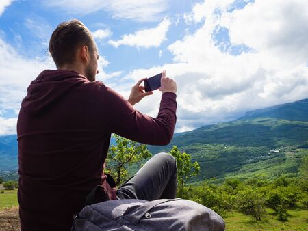 A young guy in a red hoodie and gray backpack travels in the mountains among green trees and clouds. Photographs on the phone. Banque d'images