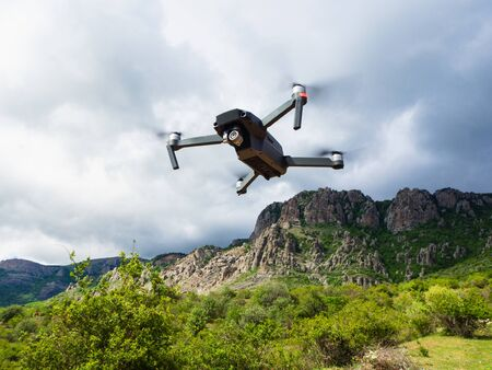 A gray drone quadrocopter with a camera flies in the mountains among the clouds.