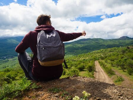 A young guy in a red hoodie and gray backpack travels in the mountains among green trees and clouds.Shows the road with his hand.