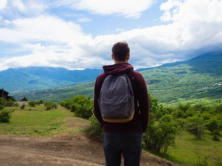 A young guy in a red hoodie and gray backpack travels in the mountains among green trees and clouds.