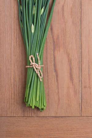 cebollin: Ajo cebolletas en mesa de madera de fondo Foto de archivo