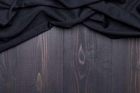 Creased black fabric texture on wooden background with copy space Фото со стока