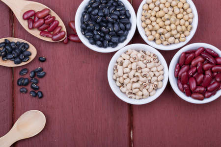 Soy beans, Red beans, black beans, and navy bean on dark wooden background