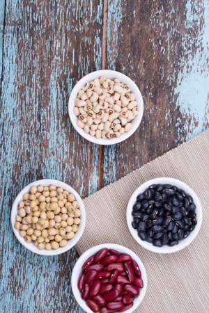Soy beans, Red beans, black beans, and navy bean on blue wooden background