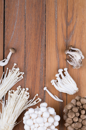 Top view of various mushrooms such as Enoki mushrooms, Brown Shimeji mushrooms and White Meech mushrooms on wooden table Фото со стока