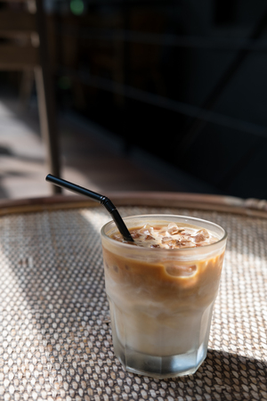 Iced Latte with straw in glass on a table in a cafe.