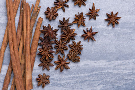 Cinnamon and Star Anise on grey texture background, top view Фото со стока