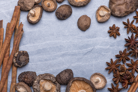 Cinnamon, Star Anise, Dried Mushroom on grey texture background with copy space, top view