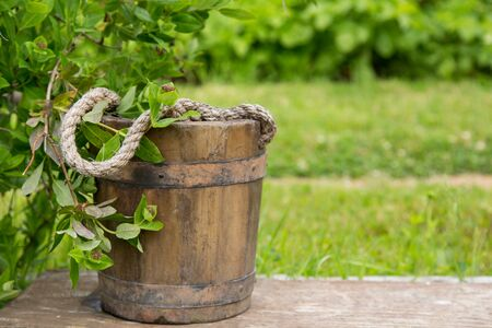 Wooden bucket with rope inside on nature green background