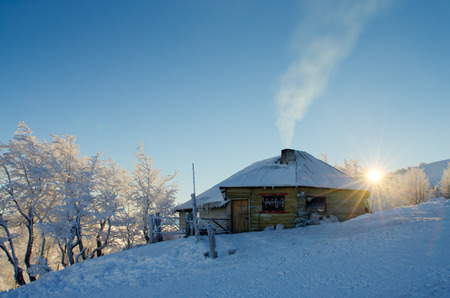 Sunrise in the mountains in winter on a cold morning. Mountain house in Carpathians, Ukraine.