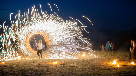 wedding night: Amazing Fire Show with a fireworks. O-shape full-round line with a lot of sparks. And rapt admirative audience around. Beautiful wedding night in Carpathian mountains in Ukraine.