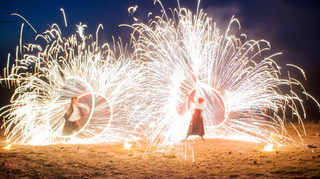 wedding night: Amazing two performers Fire Show with a fireworks. Double O-shape full-round lines with a lot of sparks. And rapt admirative audience around. Beautiful wedding night in Carpathian mountains in Ukraine.