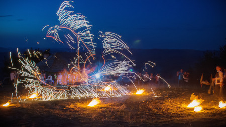 wedding night: Amazing Fire Show with a fireworks. U-shape half-round line with a lot of sparks. And rapt admirative audience around. Beautiful wedding night in Carpathian mountains in Ukraine. Stock Photo