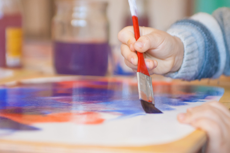Close-up of watercolor wet-on-wet paints with small kids hand holding paintbrush and drawing in Waldorf kindergarten