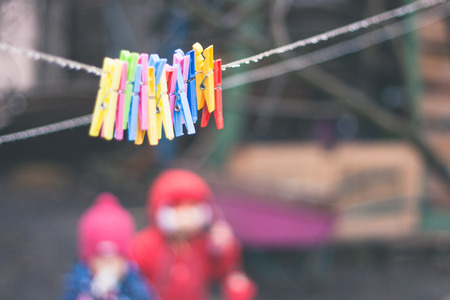plastic varicoloured clothes pins on the rope in spring rainy day with water drops and two little girls unfocused Stock Photo