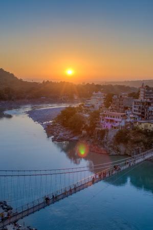 Blick auf River Ganga und Ram Jhula Brücke bei Sonnenuntergang mit einem blauen Himmel und bunte Häuser. Rishikesh Indien. HDR-Bild Standard-Bild - 76354727