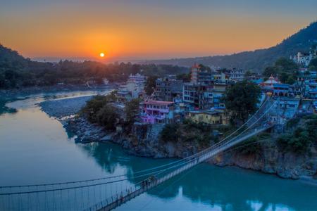 Blick auf River Ganga und Ram Jhula Brücke bei Sonnenuntergang mit einem blauen Himmel und bunte Häuser. Rishikesh Indien. HDR-Bild Standard-Bild - 76354726
