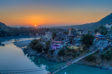 View of River Ganga and Ram Jhula bridge at sunset with a blue sky and colorful houses. Rishikesh. India. HDR image