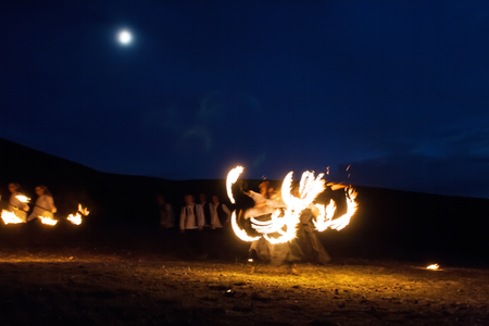 poi: Amazing Impressive Freeze light fire show with fire trails highly in mountains with a moon in a colorful blue sky