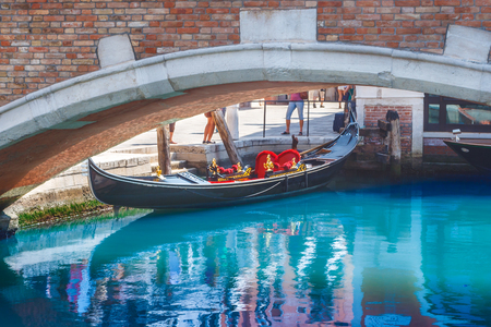 sway: Parking gondola under the brige in one of the canals of Venice, Italy. Colorful summer picture with blue water
