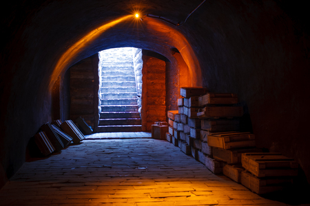 Military cellar upstairs Image from an military cellar with Stacks of old military ammunition boxes and upstairs with the sun rays coming through and a yellow lamp shining on the top. Banco de Imagens