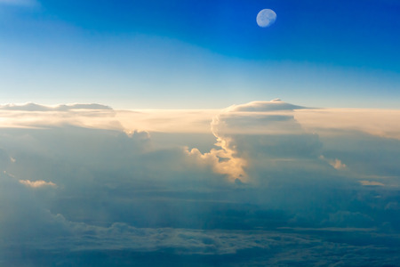 The colorful sky above the clouds with half moon airplane traveling in the summer Stock Photo