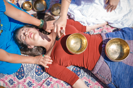 Beautiful female receiving energy sound massage with singing bowls and body massage on a river bank at spring sunny day Stock Photo