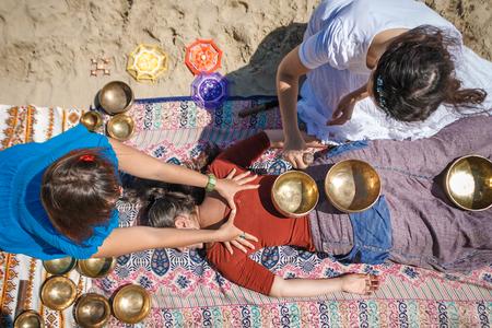 Mooie vrouwelijke ontvangende energie correcte massage met zingende kommen en lichaamsmassage op een rivierbank bij de lente zonnige dag Stockfoto